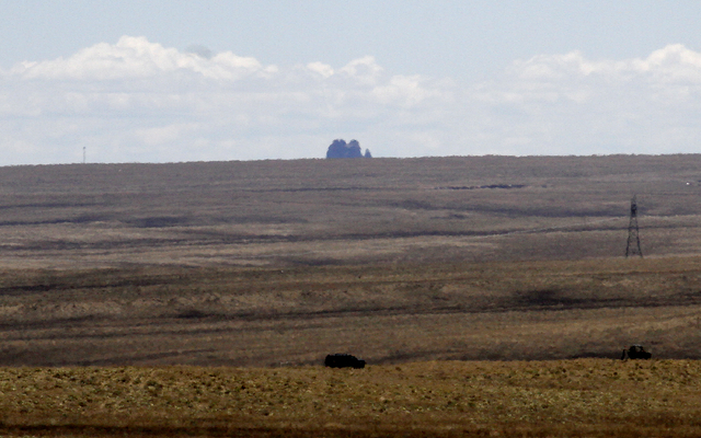 Two vehicles are seen in the distance near the area where Ashlynne Mike's body was discovered south of Shiprock, N.M., on Tuesday, May 3, 2016.  (Jon Austria/The Daily Times via AP)