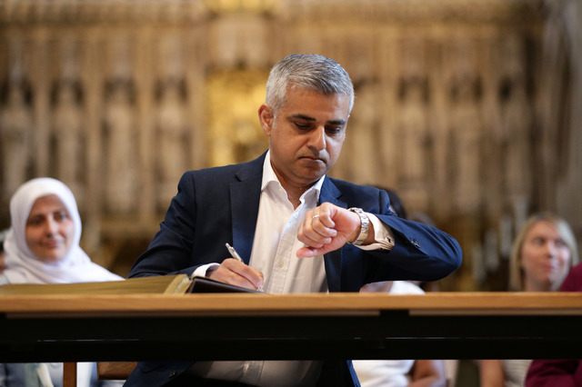 London's new mayor Sadiq Khan looks at his watch during the official signing ceremony in Southwark Cathedral, London, Saturday May 7, 2016.  (Yui Mok/Associated Press)