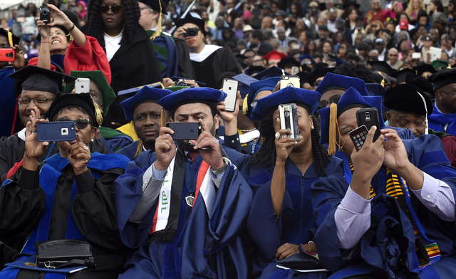 Graduates photograph President Barack Obama as he gives his commencement address to the 2016 graduating class of Howard University in Washington, Saturday, May 7, 2016.   (Susan Walsh/Associated P ...