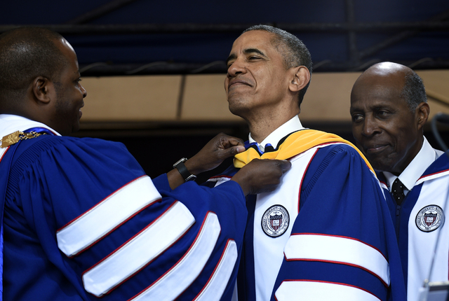 Howard University President Wayne A.I. Frederick, left, adjusts the sash of President Barack Obama, center, as he is awarded an honorary Doctor of Science degree from Howard University in Washingt ...