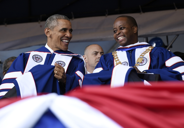 President Barack Obama, left, talks with Howard University President Wayne A.I. Frederick, right, during the commencement ceremony for the 2016 graduating class of Howard University in Washington, ...