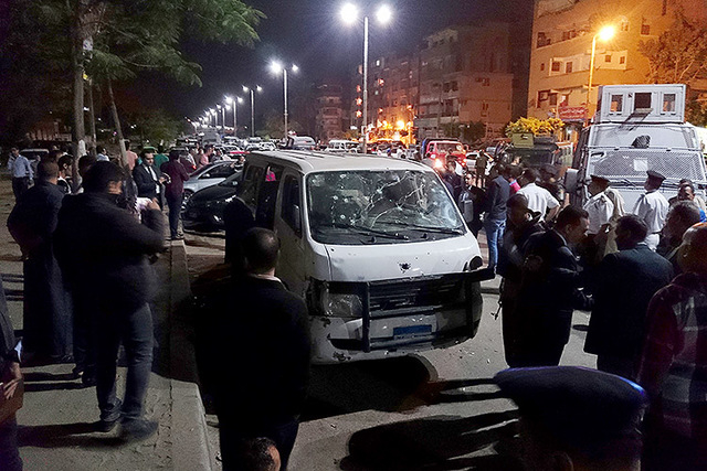 Egyptian police and civilians gather around a bullet ridden microbus in the south Cairo neighborhood of Helwan, Sunday, May 8, 2016.  (Mohsen Nabil/Associated Press)
