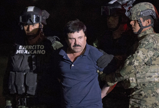 "FILE - In this Jan. 8, 2016 file photo, Mexican drug lord Joaquin ""El Chapo"" Guzman is escorted by army soldiers  to a waiting helicopter, at a federal hangar in Mexico City, after he was recaptur ..."