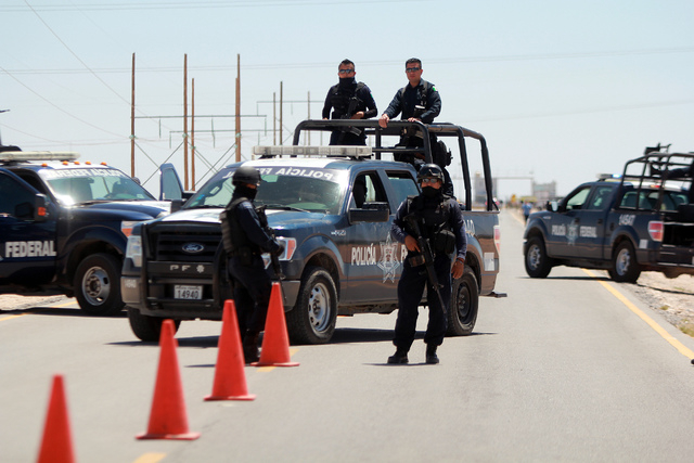 Mexican federal police guard a road leading to the Cefereso No. 9 federal prison in Ciudad Juarez, Mexico, Saturday, May 7, 2016. Convicted drug lord Joaquin El Chapo Guzman, who twice pulled off  ...