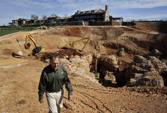 In this photo made Thursday, April 14, 2016, Johnny Morris, founder of Bass Pro Shops, walks around the edge of a massive sinkhole that opened up last spring on his golf course in Ridgedale, Mo. ( ...