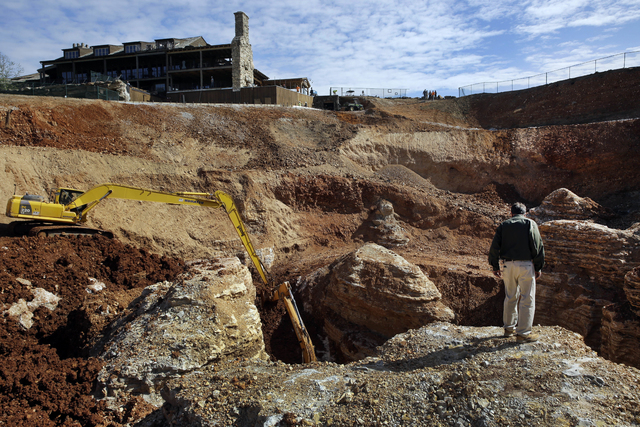 In this photo made Thursday, April 14, 2016, Johnny Morris, founder of Bass Pro Shops, looks over the edge of a massive sinkhole at his Top of the Rock Golf Course in Ridgedale, Mo.  (Jeff Roberso ...