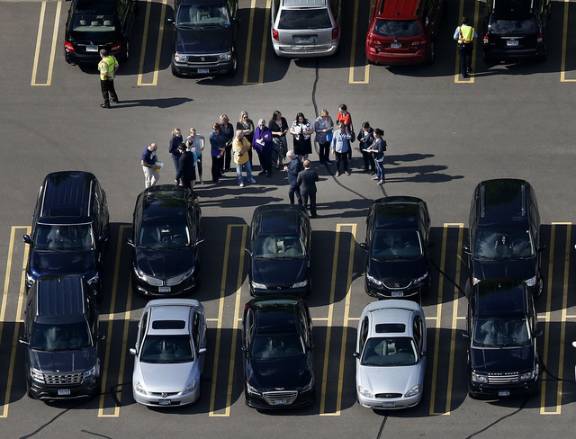 A group gathers in the parking lot at a Jehovah's Witnesses Kingdom Hall during a memorial service for Prince, Sunday, May 15, 2016, in Minnetonka, Minn. (Carlos Gonzalez/Star Tribune via AP)