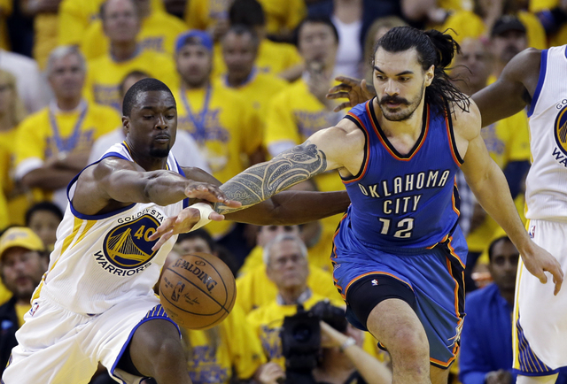 Oklahoma City Thunder's Steven Adams (12) fights for a loose ball against Golden State Warriors' Harrison Barnes (40) during the second half in Game 1 of the NBA basketball Western Conference fina ...