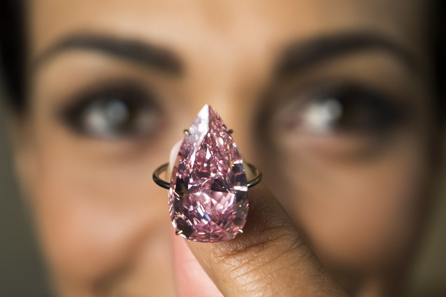 "In this  May 9, 2016 file picture a  model displays ""The Unique Pink"", the largest Fancy Vivid Pink pear shaped diamond ever offered at an auction, during a Sotheby's press preview in Geneva, Swit ..."