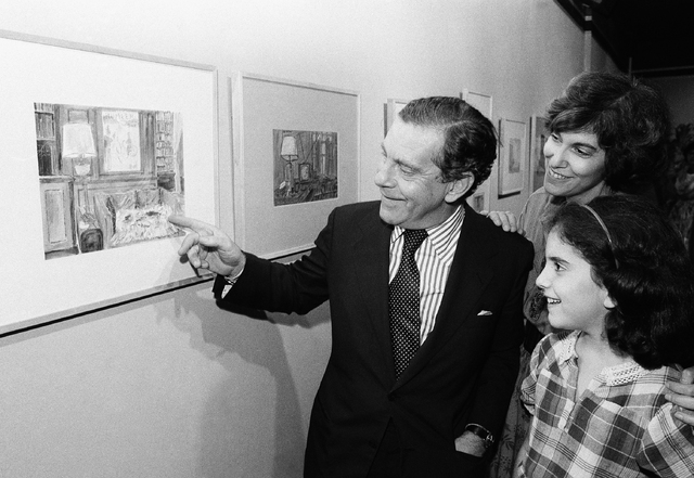 Morley Safer points to one of his watercolors displayed at a New York restaurant as his wife, Jane, and daughter, Sarah, look on, Sept. 22, 1980. (Richard Drew/AP)
