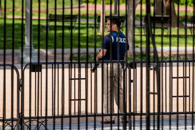 A security agent stands nearby the northwest gate of the White House in Washington, Friday, May 20, 2016, after the White House is placed on lockdown for a shooting nearby. (Andrew Harnik/AP)