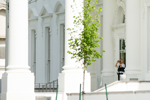 A Secret Service agent looks through binoculars as he stands at the North Portico of the White House in Washington, Friday, May 20, 2016, after the White House was placed on a security alert after ...