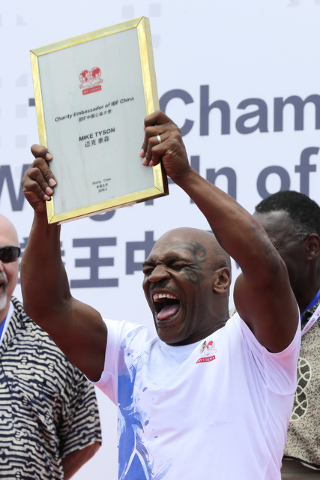 Former heavyweight boxing champion Mike Tyson reacts as he is awarded the charity ambassador of IBF China during the weigh-in ceremony of the 2016 IBF World Championship Bout at the Mutianyu secti ...