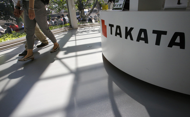 In this May 4, 2016 file photo, visitors walk by a Takata Corp. desk at an automaker's showroom in Tokyo.  Eight automakers are recalling more than 12 million vehicles in the U.S. to replace Takat ...