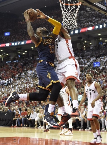 Cleveland Cavaliers forward LeBron James drives to the basket against Toronto Raptors forward James Johnson during the second half of Game 6 of the NBA basketball Eastern Conference finals, Friday ...