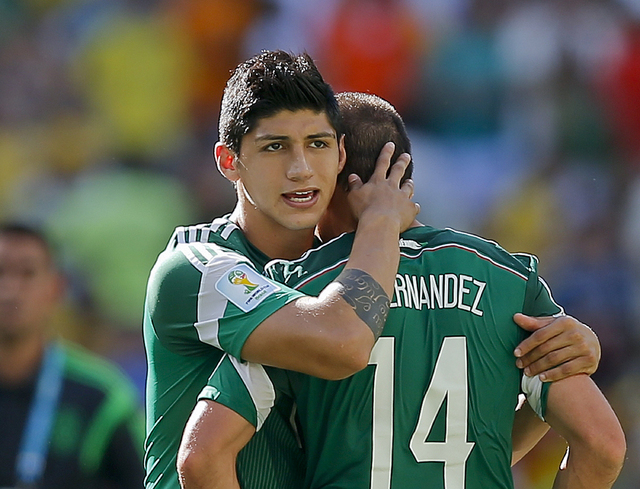 In a June 29, 2014 file photo, Mexico's Alan Pulido consoles teammate Javier Hernandez (14) after the Netherlands defeated Mexico 2-1 during the World Cup round of 16 soccer match between the Neth ...