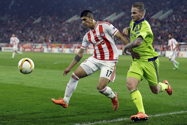 In this Thursday, Feb. 25, 2016 file photo, Olympiakos' Alan Pulido, left, fights for the ball with Anderlecht's Alexander Buttner during the Europa League round of 32 soccer match at the Georgios ...