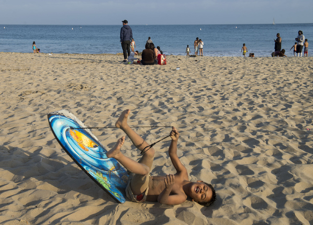 In this Sunday, May 29, 2016, photo, Gabriel Cordromp, 8, plays on the beach after beach goers were told over the loud speaker to get out of the water at Corona del Mar beach in Newport Beach, Cal ...