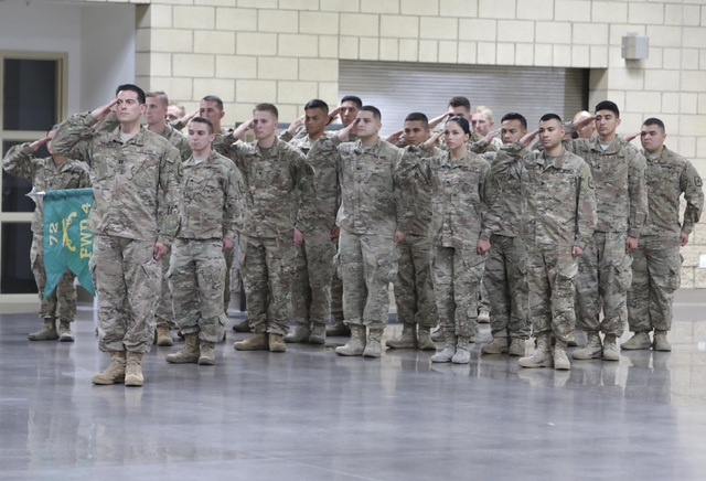 Members of the Nevada Army National Guard's 72nd Military Police Company salute during the playing of the national anthem during their homecoming ceremony at North Las Vegas Readiness Center Frida ...