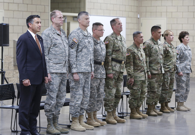 Gov. Brian Sandoval, left, Nevada's adjutant general Air Force Brig. Gen. Bill Burks, second left, and other military officials stand at attention prior to the start of a homecoming ceremony for t ...