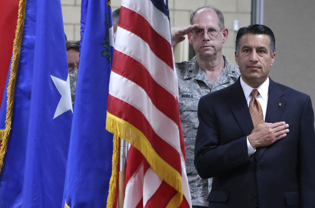 Gov. Brian Sandoval, right, places his hand over his heart as Brig. Gen. Bill Burks, salutes during the playing of the U.S. national anthem during a homecoming ceremony for the Nevada Army Nationa ...