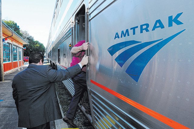 Passengers board an Amtrak train. (Don Campbell/The Herald-Palladium via AP)