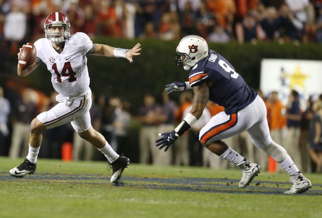 Alabama quarterback Jake Coker (14) looks to pass against Auburn defensive end Byron Cowart (9)during the second half of an NCAA college football game, Saturday, Nov. 28, 2015, in Auburn, Ala. (Bu ...