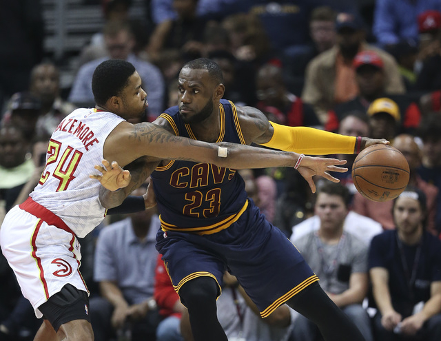 Cleveland Cavaliers forward LeBron James (23) works against Atlanta Hawks forward Kent Bazemore (24) during the first half of an NBA basketball game, in Atlanta, April 1, 2016.  (John Bazemore/AP)