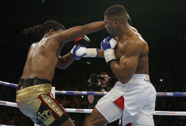 US boxer Charles Martin, left, is knocked down by British boxer Anthony Joshua during their IBF heavyweight title bout at the O2 Arena in London, Saturday, April 9, 2016.(Matt Dunham/AP)