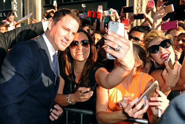 """Channing Tatum, left, takes a selfie with a fan as he arrives at the Los Angeles premiere of """"Magic Mike XXL"""" at the TCL Chinese Theatre in 2015. (Photo by Richard Shotwell/Invision/AP)"""