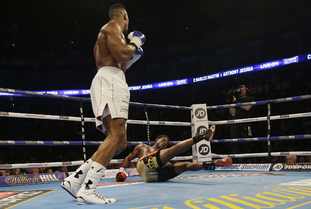 US boxer Charles Martin is knocked down by British boxer Anthony Joshua during their IBF heavyweight title bout at the O2 Arena in London, Saturday, April 9, 2016.(Matt Dunham/AP)