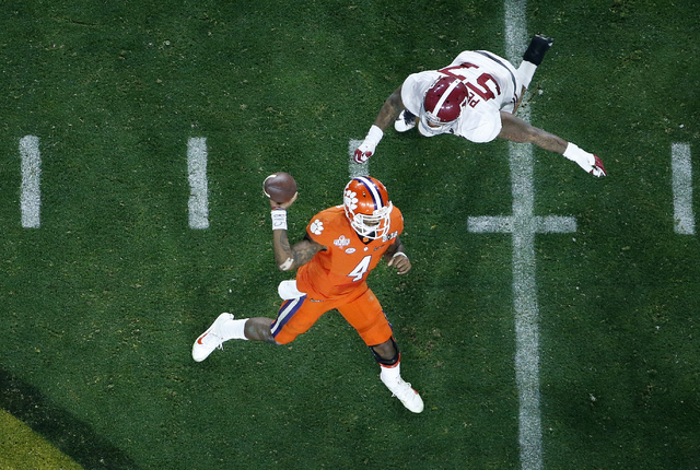 Clemson's Deshaun Watson (4) throws while being rushed by Alabama's D.J. Pettway (57) during the second half of the NCAA college football playoff championship game Monday, Jan. 11, 2016, in Glenda ...