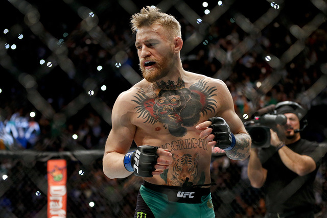 Conor McGregor warms up before fighting Jose Aldo in a featherweight  championship mixed martial arts bout at UFC 194, Saturday, Dec. 12, 2015, in Las Vegas. (AP Photo/John Locher)