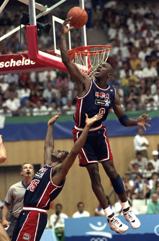 In this July 27, 1992 file photo, USA's Michael Jordan sails high above teammate Magic Johnson knocking away a shot during the first half of their preliminary round basketball game with Croatia at ...