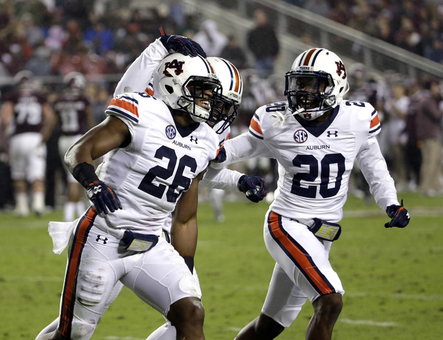 Auburn linebacker Justin Garrett (26) is congratulated by teammates Tre' Williams, center, and Jeremiah Dinson (20) after intercepting a pass against Texas A&M during the second quarter of an  ...