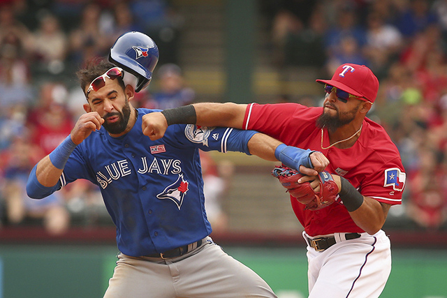Toronto Blue Jays Jose Bautista (19) gets hit by Texas Rangers second baseman Rougned Odor (12) after Bautista slid into second in the eighth inning of a baseball game at Globe Life Park in Arling ...