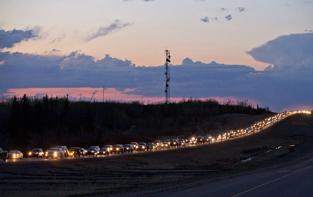 Traffic lines the highway as residents leave Fort McMurray, Alberta, Canada, on Tuesday May 3, 2016.  More than 80,000 residents were ordered to flee as a wildfire moved into the city, destroying  ...