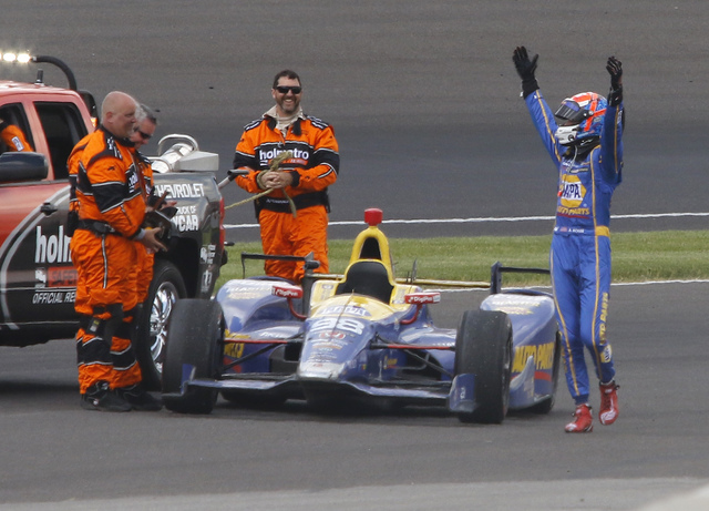Alexander Rossi celebrates as he came to a stop in the fourth turn after running out of fuel after winning the 100th running of the Indianapolis 500 auto race at Indianapolis Motor Speedway in Ind ...