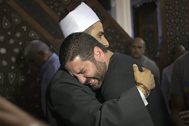 The Imam of al Thawrah Mosque, Samir Abdel Bary, gives condolences to film director Osman Abu Laban, center, who lost four relatives, all victims of Thursday's EgyptAir plane crash, following pray ...