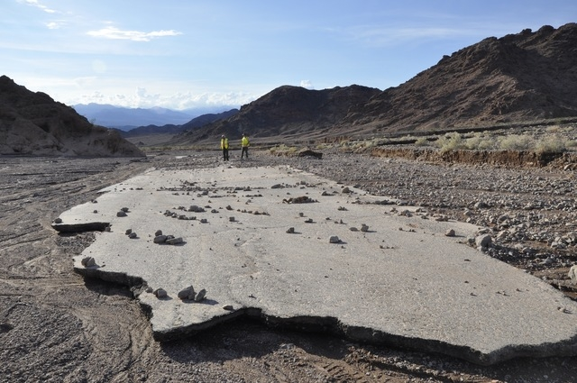 In this undated photo from October, workers inspect a stretch of Badwater Road washed away by flooding in southern Death Valley National Park. (National Park Service)