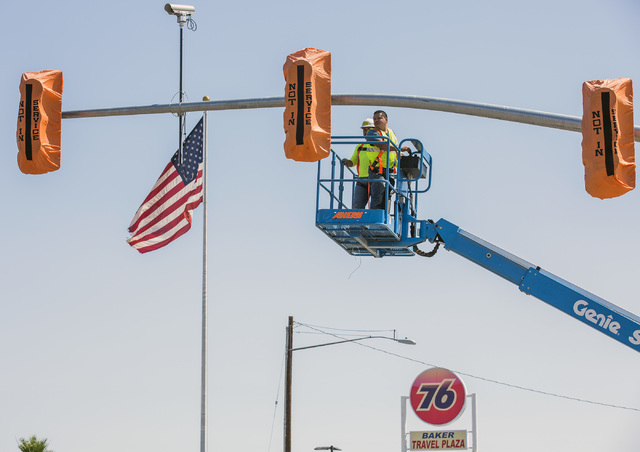 A work crew installs the first traffic light in Baker, Cal. on Monday, May, 23, 2016. The owner of Baker Travel Plaza spent four years trying to install the signal because it is cheaper than a tra ...
