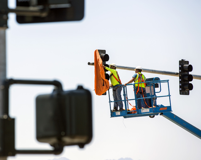 A work crew removes the cover from the first traffic light in Baker, Cal. on Monday, May, 23, 2016. The owner of Baker Travel Plaza spent four years trying to install the signal because it is chea ...