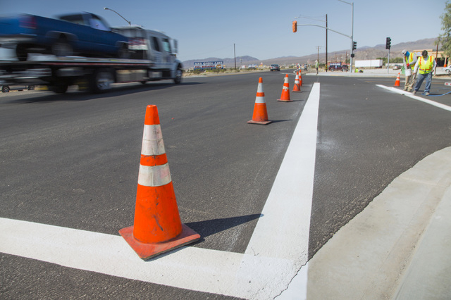 A work crew paints pedestrian walkway at the first traffic light in Baker, Cal. on Monday, May, 23, 2016. The owner of Baker Travel Plaza spent four years trying to install the signal because it i ...