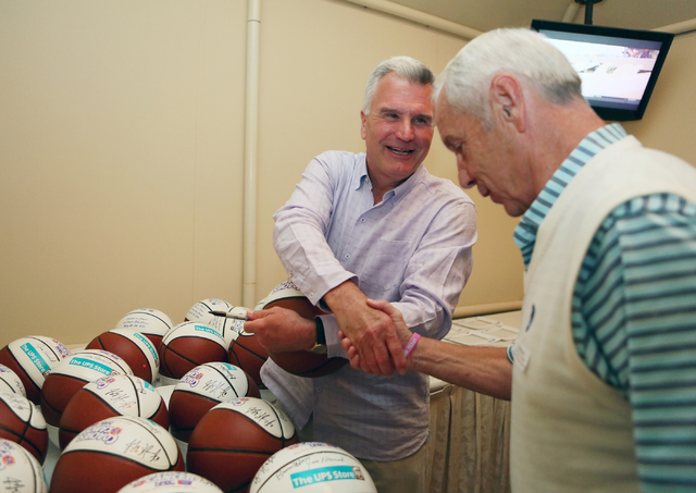 Kansas State coach Bruce Weber, left, shakes hands with North Carolina coach Roy Williams in a basketball signing tent at the 9th annual Coaches vs. Cancer Las Vegas Golf Classic hosted at MGM Gra ...