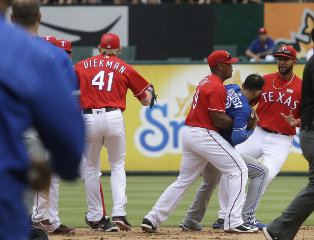 Texas Rangers third baseman Adrian Beltre (29) holds onto Toronto Blue Jays right fielder Jose Bautista (19) during  a fight in the eighth inning of a baseball game in Arlington, Texas, Sunday, Ma ...