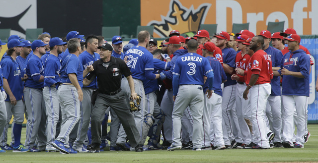Texas Rangers and Toronto Blue Jays tussle during the eighth inning of a baseball game in Arlington, Texas, Sunday, May 15, 2016. (LM Otero/AP)