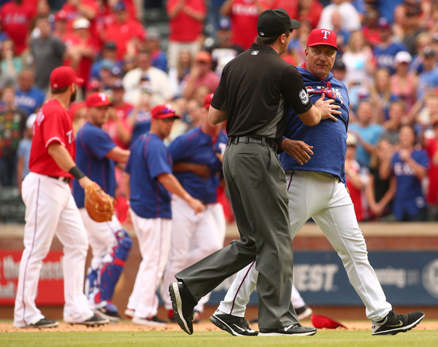 Umpire Lance Barrett (94) holds back Texas Rangers manager Jeff Banister (28) after a bench-clearing fight broke out in the 8th inning against the Toronto Blue Jays in Arlington, Texas, Sunday May ...