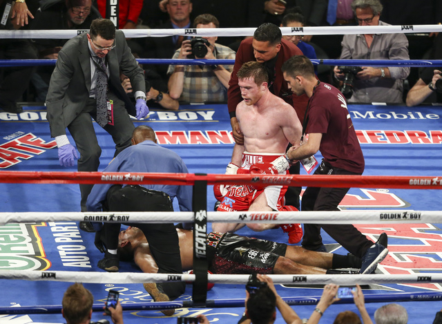 Canelo Alvarez, right, looks over at an unconscious Amir Khan during their the WBC middleweight championship fight at T-Mobile Arena in Las Vegas on Saturday, May 7, 2016. Alvarez won with a knock ...