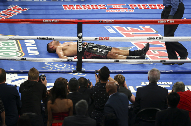 Amir Khan lies on the mat after being knocked unconscious by Canelo Alvarez in their the WBC middleweight championship fight at T-Mobile Arena in Las Vegas on Saturday, May 7, 2016. Alvarez won wi ...