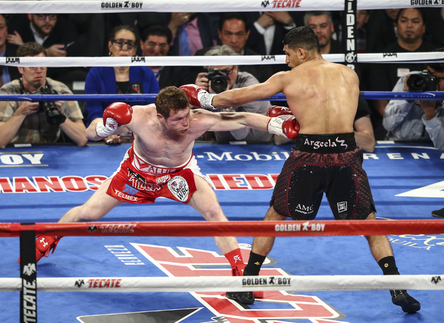 Canelo Alvarez, left, hits Amir Khan during their the WBC middleweight championship fight at T-Mobile Arena in Las Vegas on Saturday, May 7, 2016. Alvarez won with a knockout in the 6th round.  (C ...